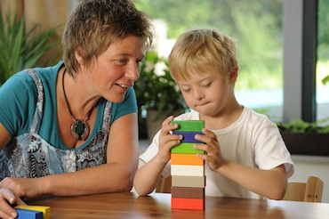Teacher works with student stacking building blocks
